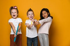 Dental hygiene. happy little cute children with toothbrushes. Three joyful friends of children hold toothbrushes. The concept of health, oral hygiene, people stock photos