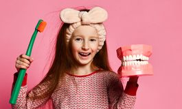Dental hygiene. happy little cute girl with toothbrushes. Red-haired pretty girl in pajamas with a toothbrush and a kissuos mock-up with scales stand over a stock image