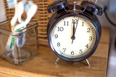 Dental hygiene time concept. Black alarm clock in the washroom stock photo