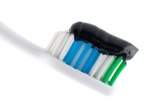 Dental Hygiene And Tooth Care. A toothbrush with black toothpaste over white in a dental hygiene and tooth care concept Stock Photo