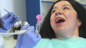 Dental hygienist provides root planing for patient stock image