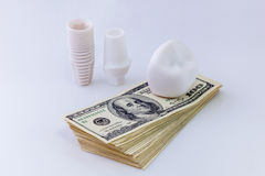 Dental implant on money. The dental implant construction is laying on the pack of dollars on white background Stock Image