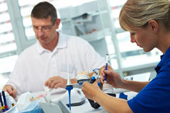In a dental lab. Two dental technicians working in a dental laboratory royalty free stock images