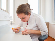 Dental Lab. Female dental technician attaching a wax crown in a muffles royalty free stock image
