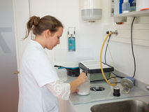 Dental Lab. Female dental technician mixing casting compound stock photo