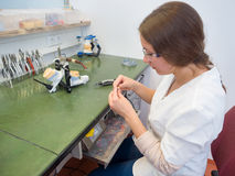 Dental Lab. Female dental technician polishing a tooth crown stock images