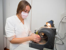 Dental Lab. Female dental technician polishing a tooth crown stock photography