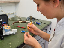 Dental Lab. Female dental technician working on a wax crown royalty free stock photos