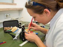 Dental Lab. Female dental technician working on a wax crown royalty free stock photography