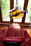 Dental Lamp and Chair. A red dental chair and light at a dentists office royalty free stock images
