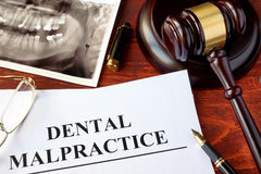 Dental Malpractice form, and gavel. Dental Malpractice form, and gavel on a surface stock image