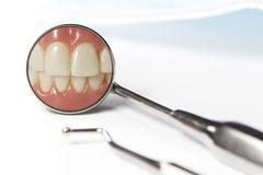 Dental mirror displays image of teeth beside pick. Dental mirror displays image of clenched front teeth beside metal pick and mask on white table Stock Photography