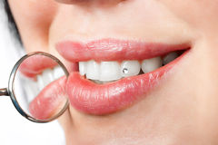 Dental mouth mirror near healthy white woman teeth
