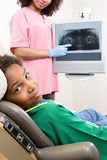 Dental nurse showing patient x ray Stock Images