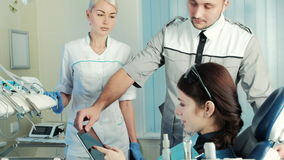 In the dental office doctor and nurse showing patient treatment plan. stock footage