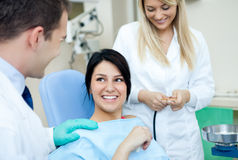 Dental practice. Male dentist, his assistant and female patient in dental practice Stock Image
