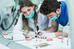 Dental prosthesis, dentures, prosthetics work. Prosthetics hands while working on the denture, false teeth, a study and a table wi Royalty Free Stock Photography