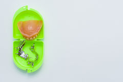 Dental prosthesis and skeletal pieces over a green box. With white background Royalty Free Stock Photos
