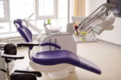 Dental Room with Modern Equipment. Interior of modern dental room: cozy chair and dentistry equipment waiting for patient, panoramic windows royalty free stock images