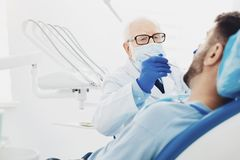 Professional male dentist diagnosing patient stock photo