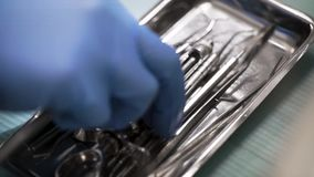 Dental surgeon is choosing and taking steel sterile tool from metal box in operating room, closeup of hand. Details during operation stock video