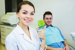 Dental surgeon and patient smiling happy after dental checkup, looking at camera. Royalty Free Stock Photos