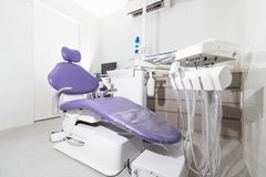 A dental surgery room with a dental chair with purple upholstery. Description: A compact dental surgery room with white wall and dental chair with purple royalty free stock images