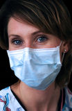 Dental Tech with Mask. Pretty blue-eyed woman with dental technician's mask on, over black Royalty Free Stock Photos