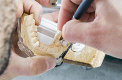 Dental technician applying ceramics to teeth in the dental model Royalty Free Stock Image