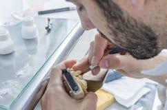 Dental technician applying ceramics to teeth in the dental model Stock Photo