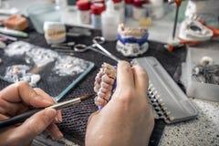 Dental technician applying ceramics Royalty Free Stock Images