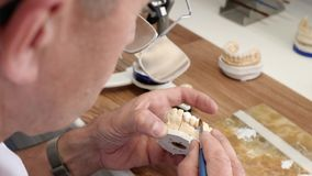 Dental technician in eyeglasses draws white ceramics glaze on prosthesis of teeth in workplace in laboratory. Of implants stock video footage