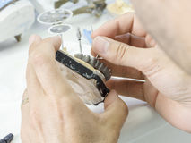 Dental technician making a metal structure of a dental crown or. Bridge stock images