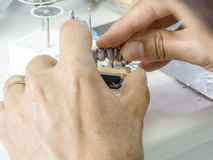 Dental technician making a metal structure of a dental crown or. Bridge royalty free stock images