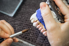 Dental technician is painting stock image