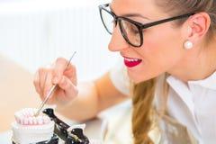 Dental technician producing denture. Female dental technician or orthodontist  producing denture with imprint Stock Image