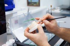 Dental technician`s hands stock image