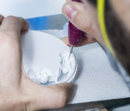 dental technician using dental burs with zirconium teeth. Stock Image