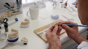 Dental technician on work draws white paint on artificial teeth in laboratory of implant production