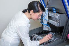 Technician in a dental lab working at a drilling or milling machine Stock Images
