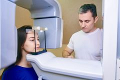 Girl-patient stands in a tomograph, a doctor near the control panel royalty free stock image