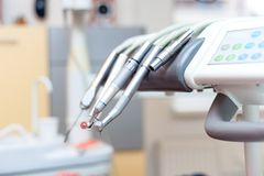 Dental tools on dentist chair with medical equipment Royalty Free Stock Photo