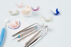 Dental tools and retainer. Dental  tools  and retainer orthodontic appliance on the blue background Royalty Free Stock Photos