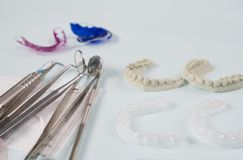 Dental tools and retainer. Dental  tools  and retainer orthodontic appliance on the blue background Stock Photo