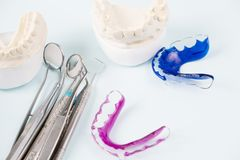 Dental tools and retainer. Dental  tools  and retainer orthodontic appliance on the blue background Royalty Free Stock Image