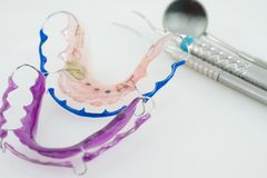 Dental tools and retainer. Dental  tools  and retainer orthodontic appliance on the white background Royalty Free Stock Photos