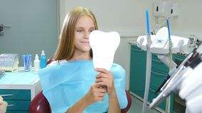 Dental tooth health concept. Portrait of smiling girl looking at mirror sitting on dental chair. Treatment in medical. Dental clinic. Health and dental care stock video footage