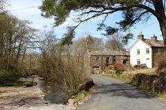 Dentdale minor road, cottages and rocky river bed. Roadside barn and cottage at Arten Gill in Dentdale, Cumbria, England. The minor road follows the River Dee Royalty Free Stock Images