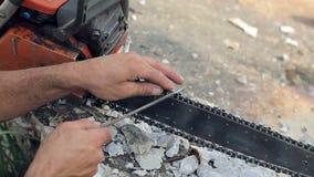 Dente da serra de cadeia que aponta para o corte de madeira O trabalhador aponta a serra de cadeia com um close-up de moedura da  filme