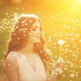 Dente-de-leão de sopro da jovem mulher bonita Moça na moda em s Imagem de Stock